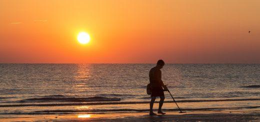Une personne utilise un détecteur de métaux sur la plage